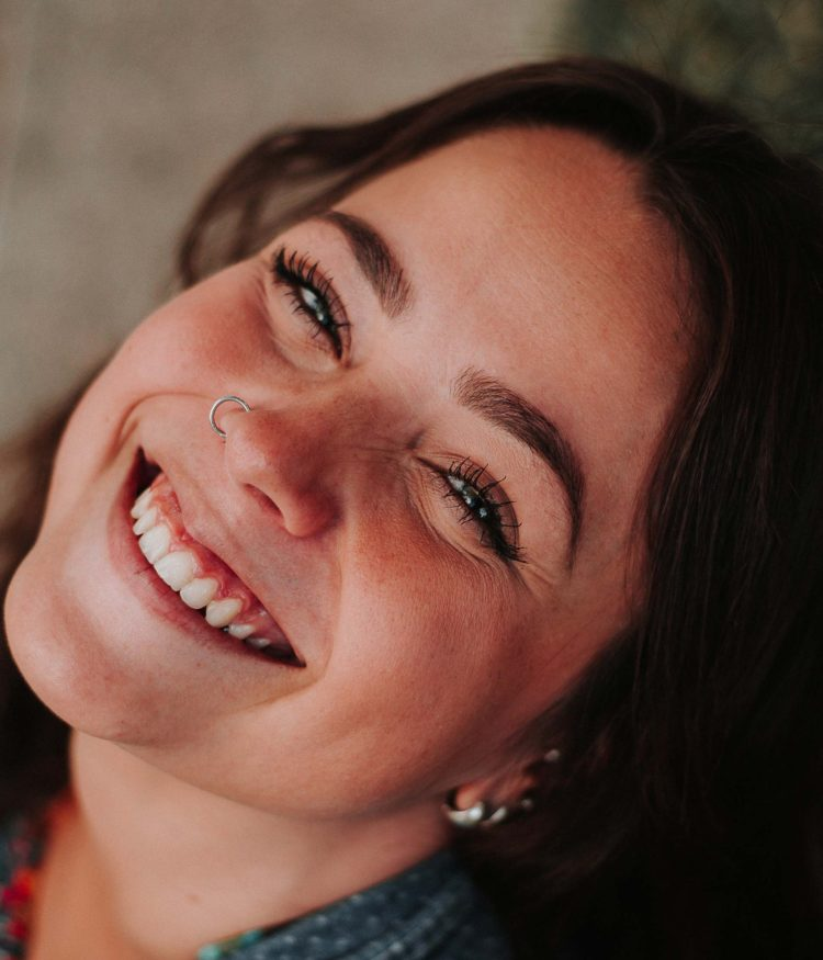Young smiling woman with a new nose piercing and makeup