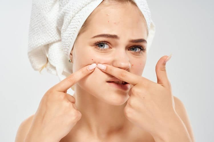 Girl picking pimples on her face