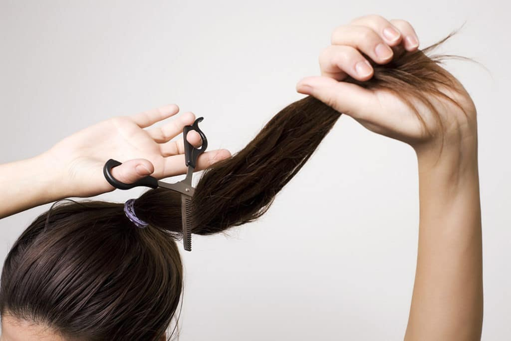 Girl cutting her hair with the ponytail method