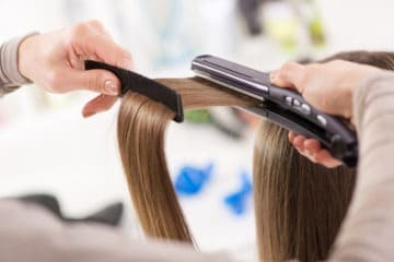 Girl using a straightening iron to straight her hair