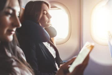 Girl reading a book on an airplane on why skin breaks out when flying on an airplane