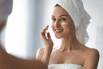 Woman applying face mask cream on her face