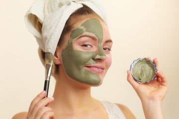 Girl applying clay mask to her face to get rid of oil on her nose and forehead