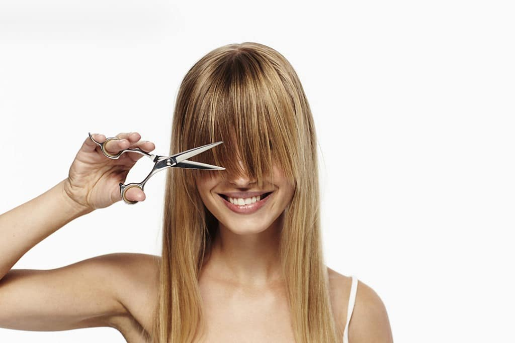 Girl cutting her bangs by her self