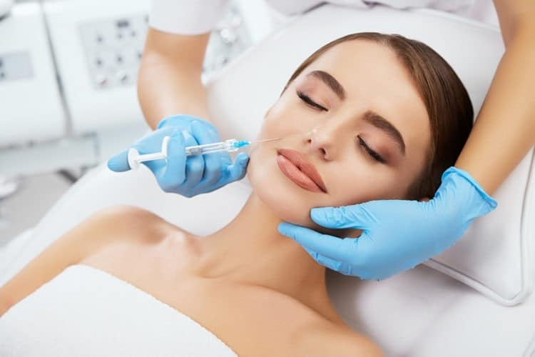 Girl being injected with filler in her face